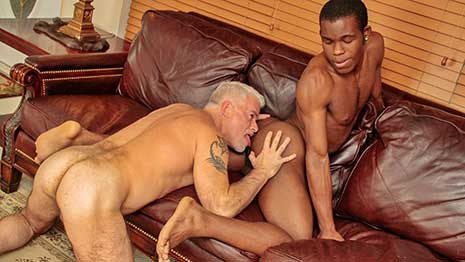Zion Jay Prescott and Jake Marshall kiss passionately on the couch. Zion plays with Jakes nipples, then unzips Jake's jeans to get at daddy's cock. Jake stands up while Zion blows his prick.